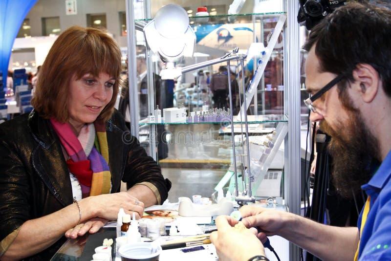 A mulher olha como um funcionamento do técnico dental foto de stock