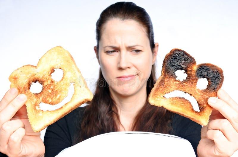 A mulher olha duas fatias diferentes de pão do brinde fotografia de stock