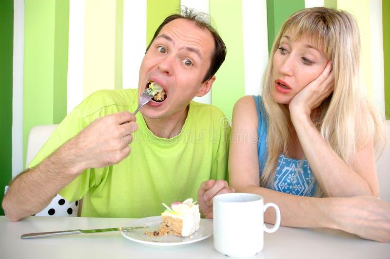 A mulher olha enquanto o homem come um bolo fotografia de stock
