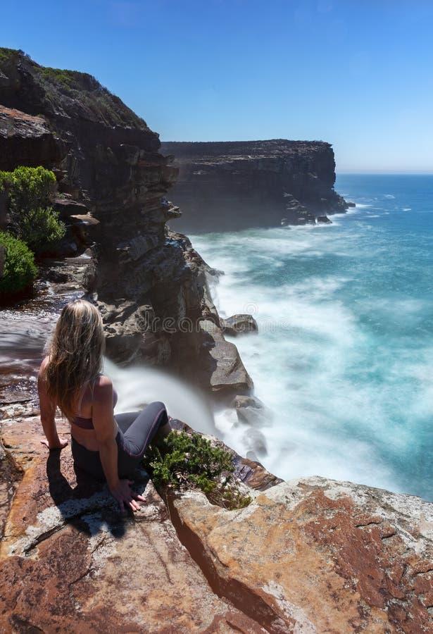 A mulher olha fluxos da cachoeira fora dos penhascos no oceano fotos de stock