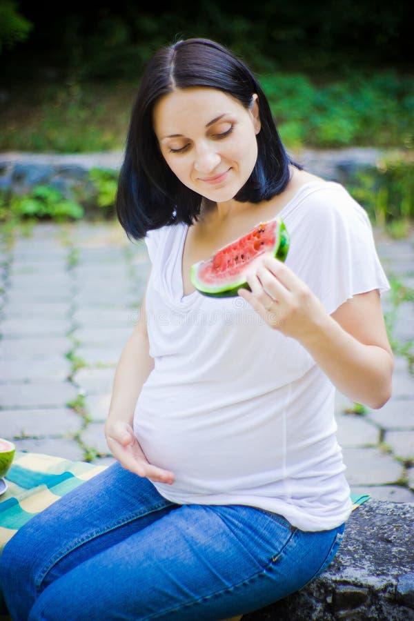 A mulher olha na melancia foto de stock