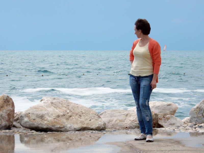 A mulher olha o mar imagem de stock