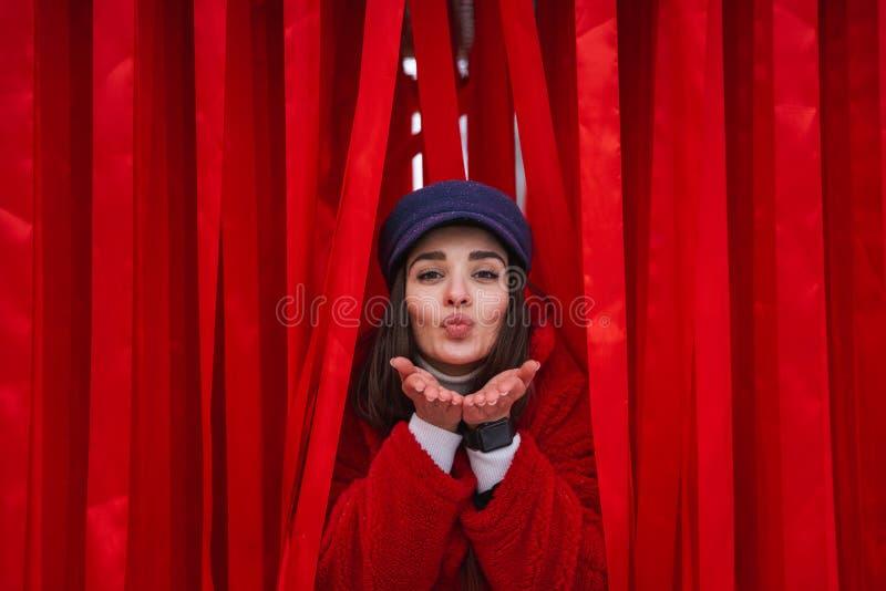 A mulher olha para fora entre a cortina vermelha imagens de stock