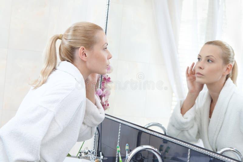 A mulher olha seu auto no espelho fotografia de stock