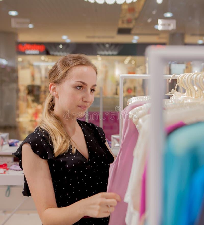 A mulher olha sobre a roupa Anuncie, venda, conceito da forma Mulher que está na loja, olhando ganchos com roupa, choosin fotos de stock