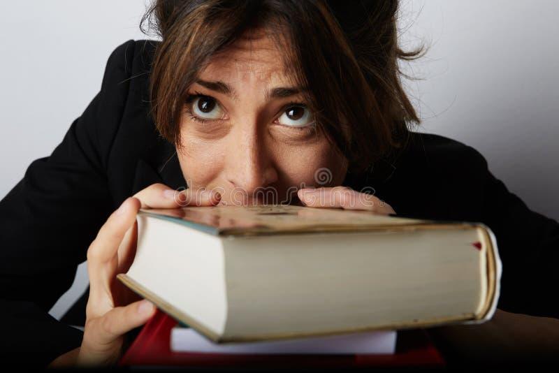 Mulher oprimida nova que estuda duramente Estudante novo cansado, forçado e sobrecarregado Modelo fêmea entre uma pilha enorme de imagens de stock royalty free
