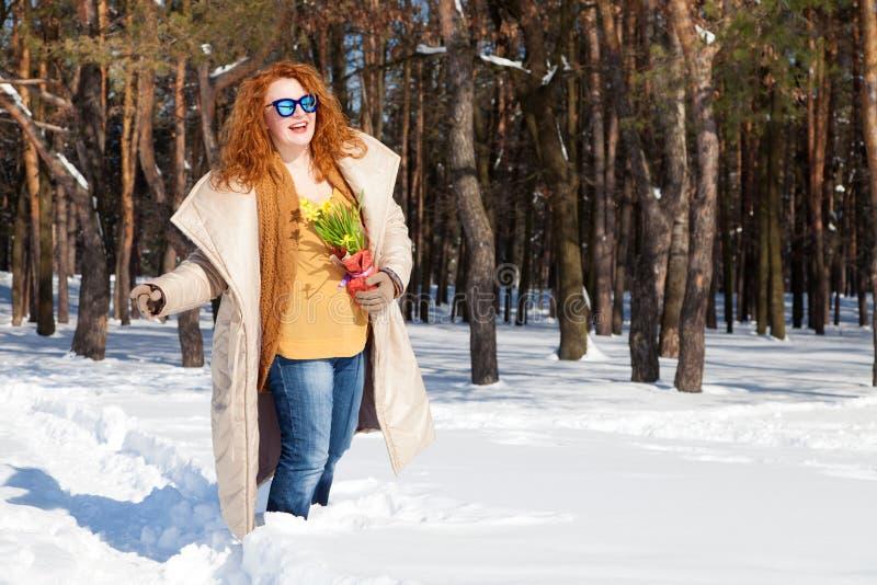 Mulher otimista que anda através da floresta nevado com o ramalhete do narciso amarelo fotos de stock