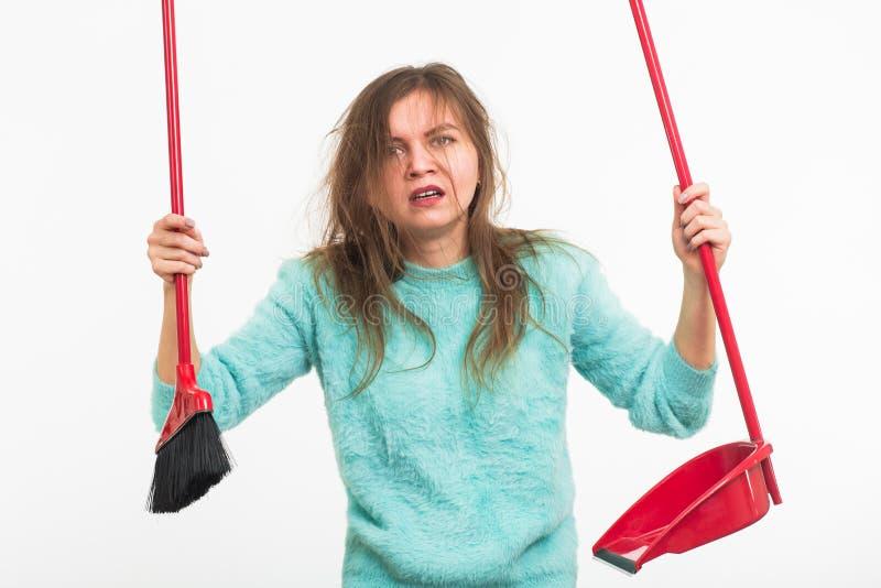 Mulher ou dona de casa que guardam a vassoura, cansado à limpeza, no fundo branco, isolado com o espaço da cópia foto de stock