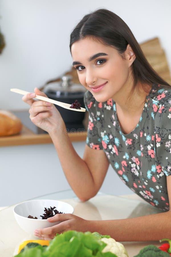 Mulher ou estudante latino-americano novo que cozinham na cozinha Menina que prova a salada fresca ao sentar-se na tabela imagem de stock