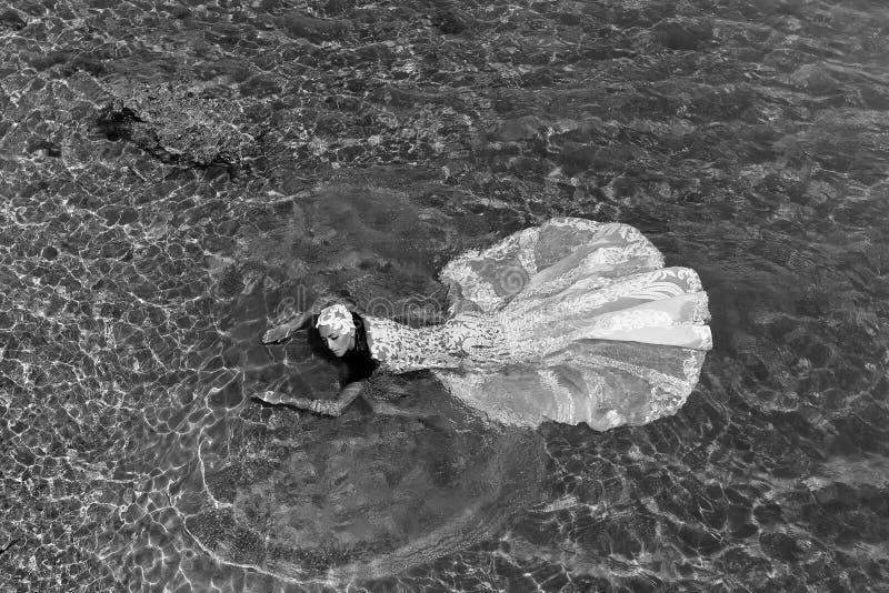 Mulher ou noiva do casamento no vestido branco na água do mar fotos de stock royalty free
