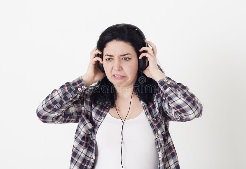 A mulher ouviu uma música muito má ou um ruído desagradável nos fones de ouvido, ela torceu a cara e quê-la remover os fones de o fotografia de stock royalty free