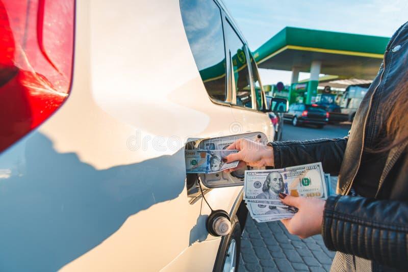 A mulher pôs o dinheiro ao tanque do carro subida de preços da gasolina imagens de stock
