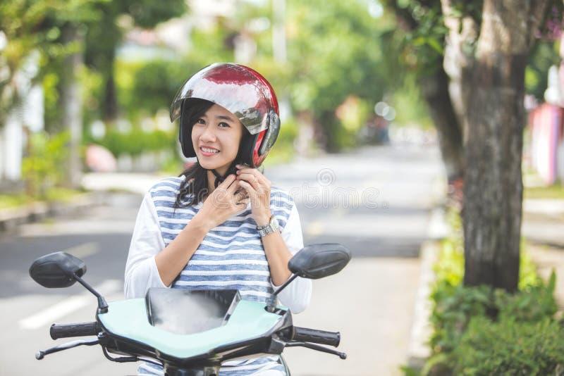 A mulher pôs seu capacete sobre antes de montar um velomotor imagem de stock royalty free