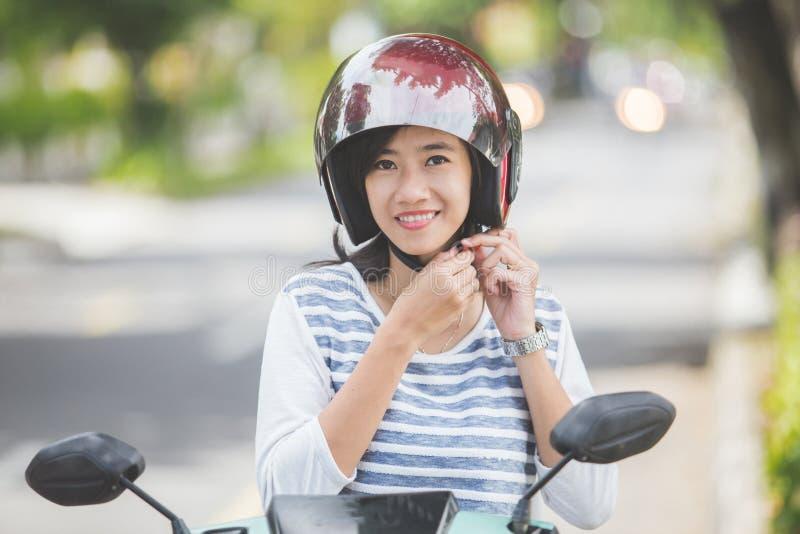 A mulher pôs seu capacete sobre antes de montar um velomotor imagem de stock
