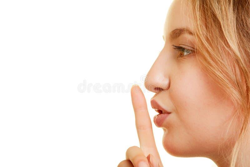 A mulher põe o dedo sobre a boca como o gesto da calma e do silêncio imagem de stock royalty free