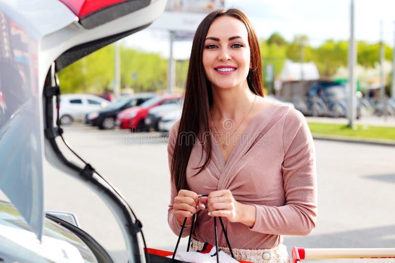 A mulher põe sacos do carrinho de compras ao tronco imagens de stock