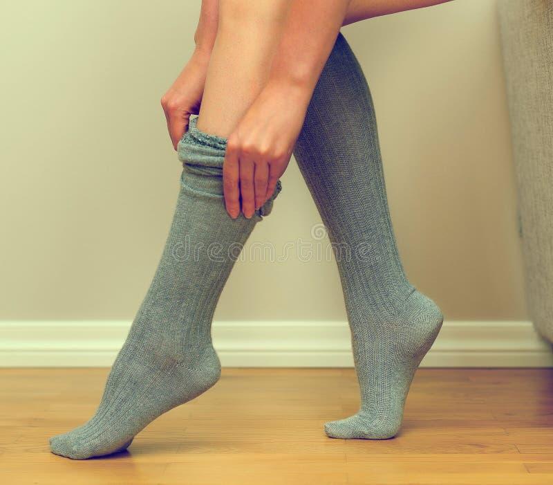A mulher põe sobre suas meias fotos de stock royalty free
