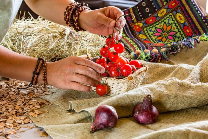 A mulher põe tomates sobre a tabela foto de stock royalty free