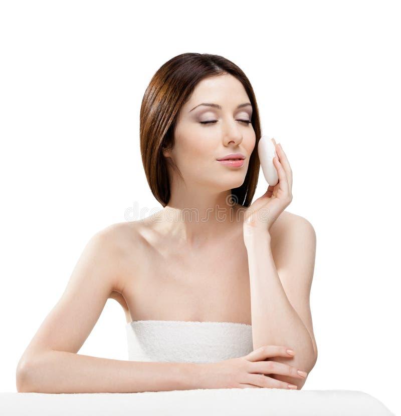 A mulher pôr sua face sobre com esponja foto de stock