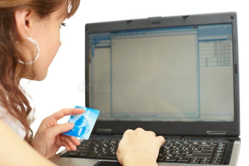 A mulher paga o cartão de crédito ao comprar em linha foto de stock