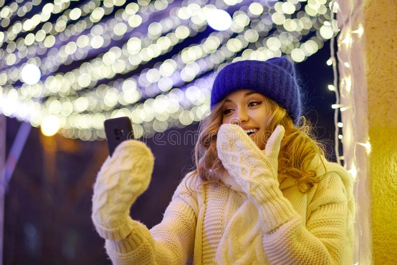 Mulher parabenizando com Natal ou Ano Novo Mulher com smartphone na Festive Fair imagens de stock