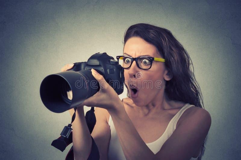Mulher parecendo jovem engraçada com câmara digital fotografia de stock