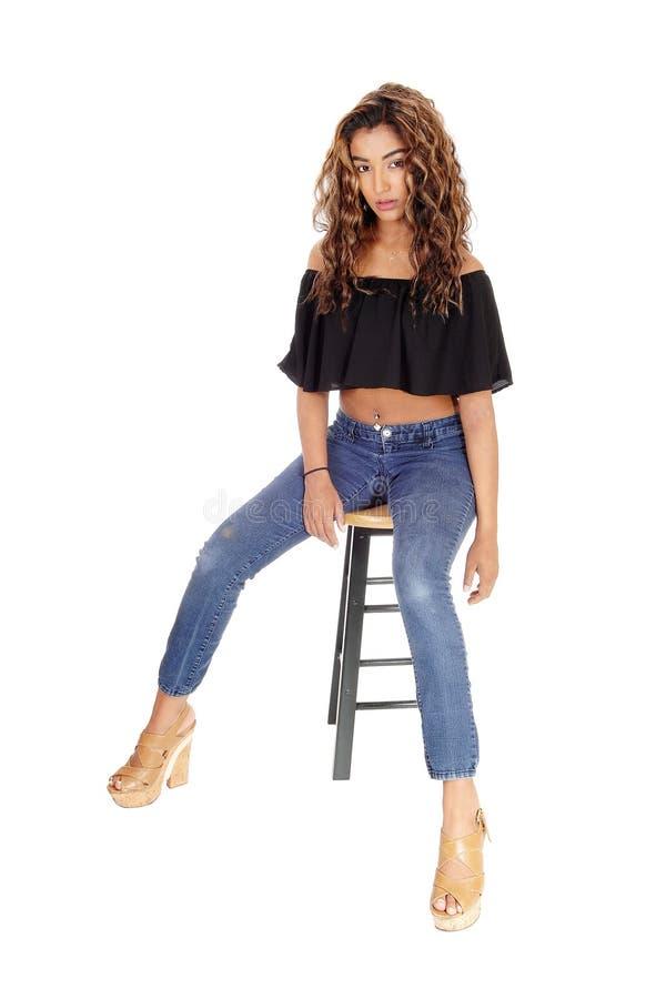 Mulher parecendo jovem séria que senta-se na cadeira da barra imagem de stock