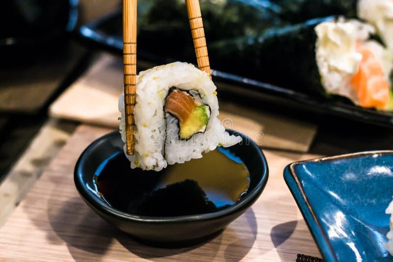 A mulher pegara o rolo de sushi de Uramaki com salmões frescos, abacate e queijo de Philadelphfia, coberto com as sementes de sés foto de stock