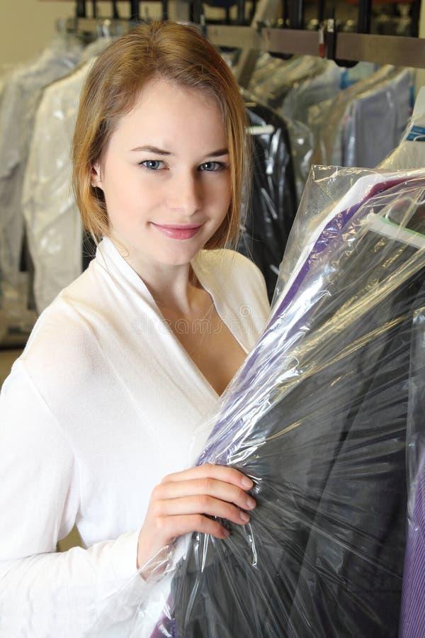 A mulher pegara a roupa em uma tinturaria imagens de stock royalty free