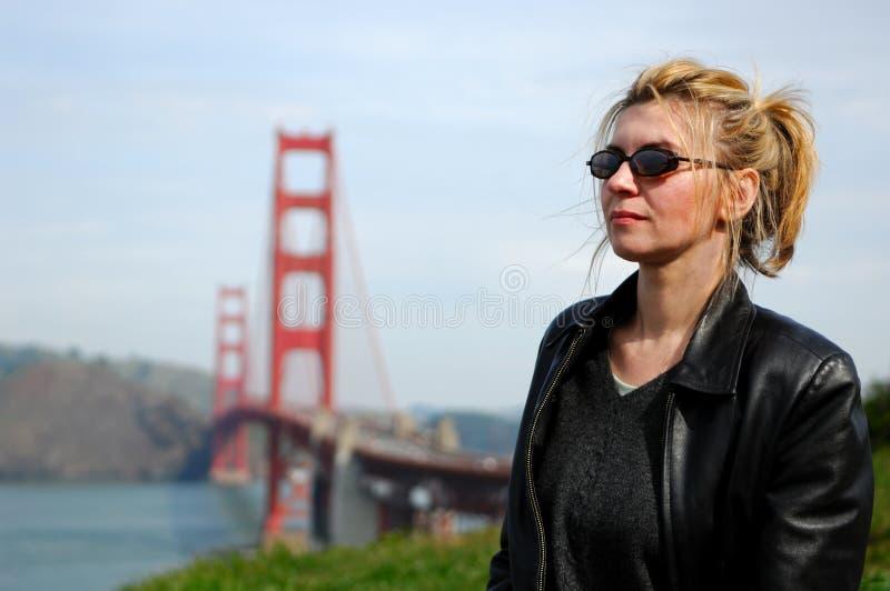 Mulher pela ponte de porta dourada imagem de stock royalty free