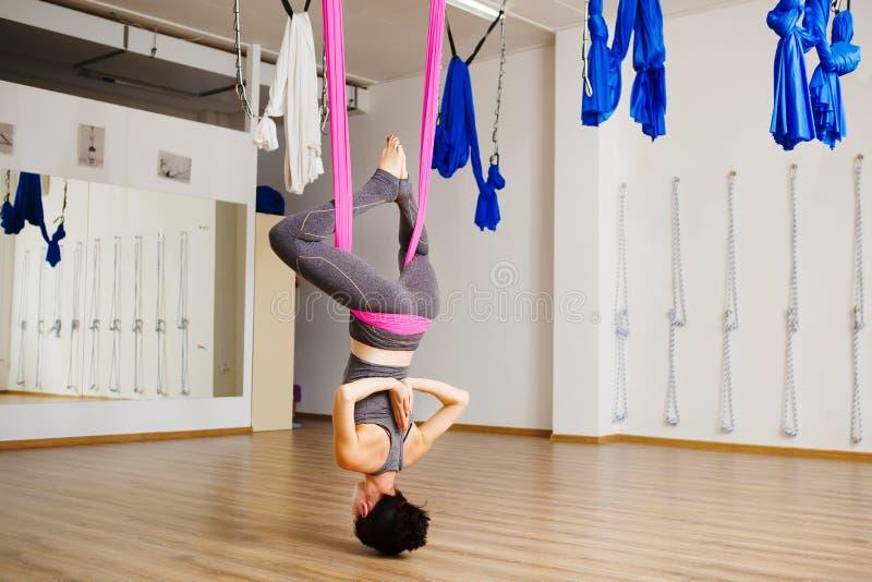 A mulher pendura anti exercícios aero fazendo de cabeça para baixo da ioga da gravidade imagens de stock royalty free