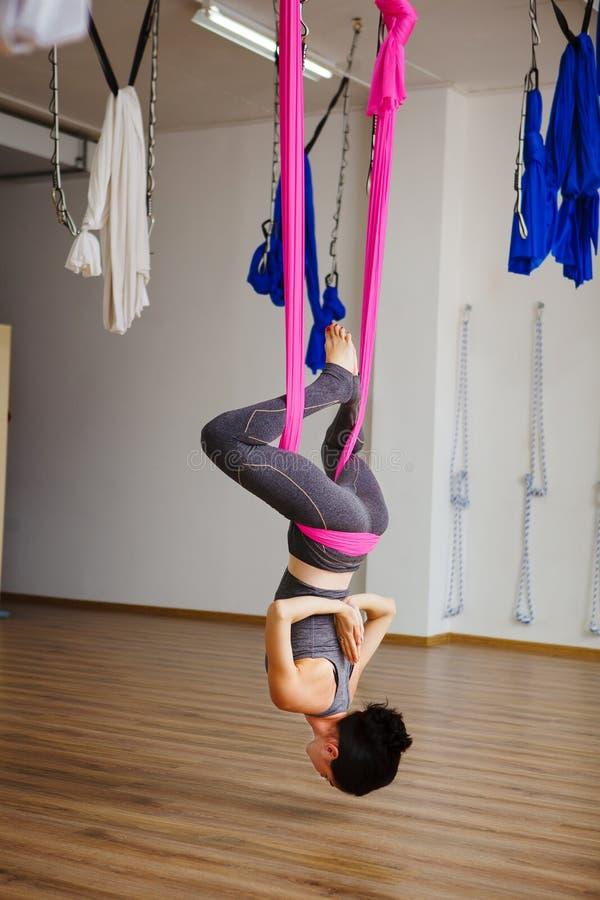 A mulher pendura anti exercícios aero fazendo de cabeça para baixo da ioga da gravidade imagem de stock royalty free