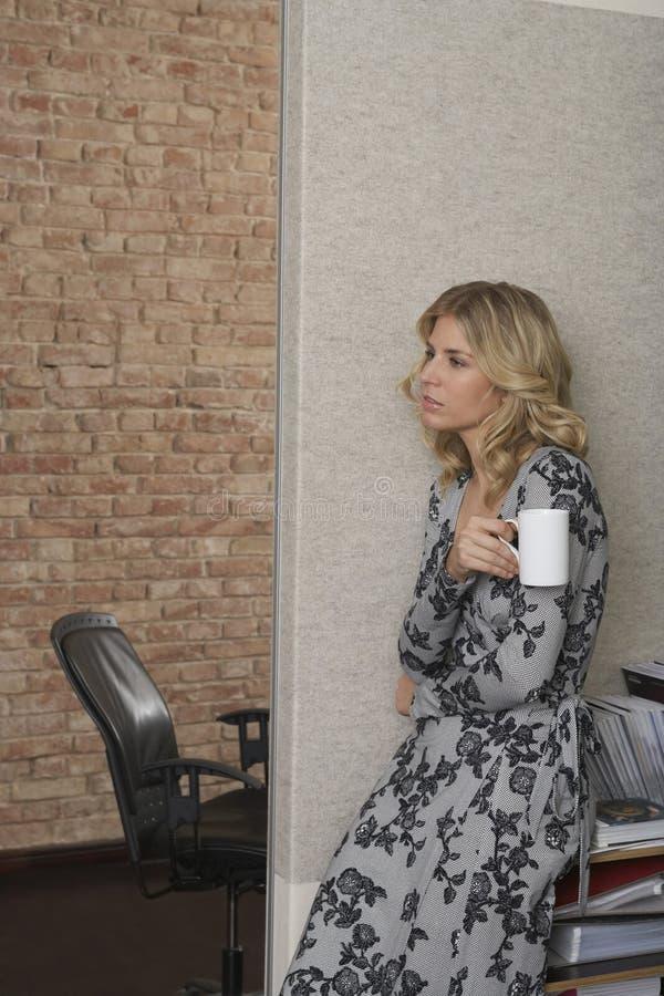 Mulher pensativa com a caneca no escritório imagem de stock royalty free