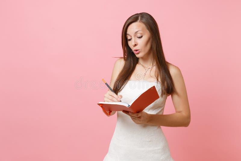 Mulher pensativa da noiva em notas planejando no diário, escolha da escrita do casamento do vestido de casamento do caderno do ca imagem de stock