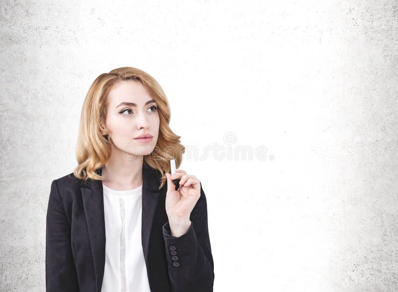 Mulher pensativa do gengibre com marcador, muro de cimento fotos de stock royalty free