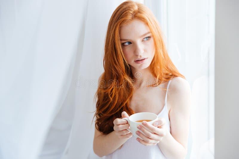 Mulher pensativa do ruivo que guarda o copo com chá fotografia de stock royalty free