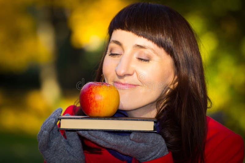 Mulher pensativa e sonhadora que guarda a maçã e o livro frescos no parque outonal, conceito do outono foto de stock royalty free