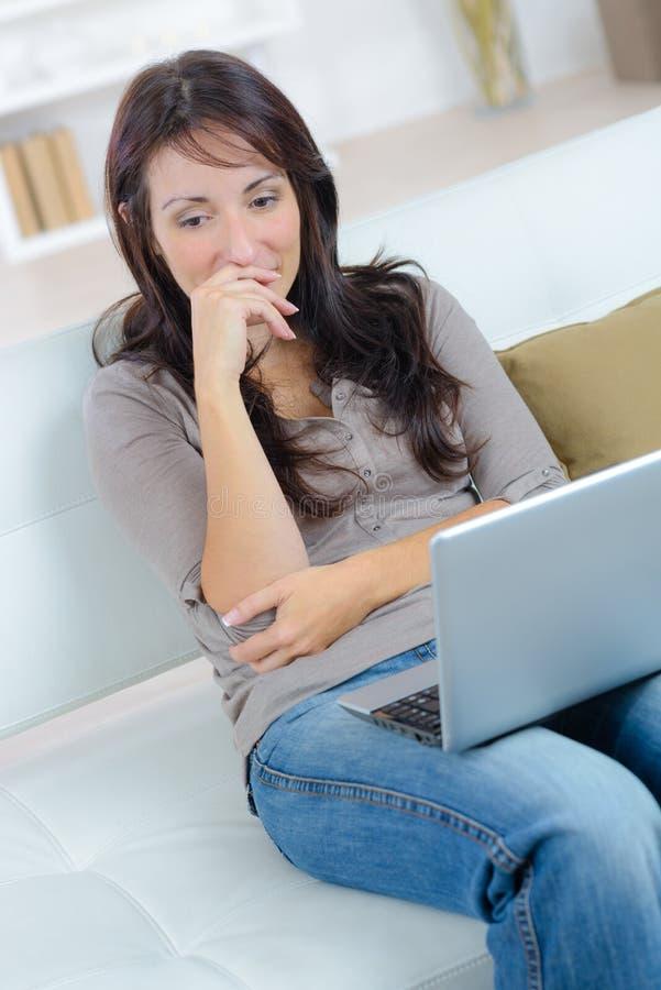 Mulher pensativa feliz que senta-se no sofá com portátil foto de stock