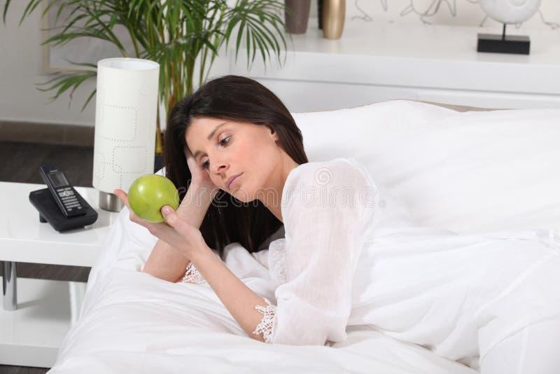 Mulher pensativa na cama fotografia de stock