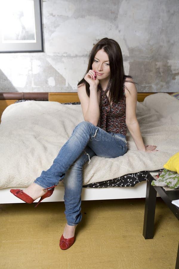 Mulher pensativa nas calças de brim e em sapatas vermelhas fotos de stock royalty free