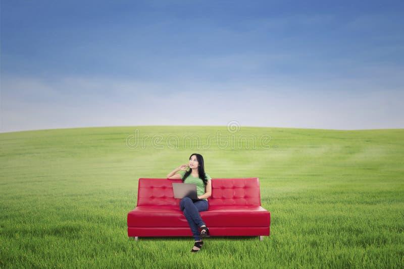 Mulher pensativa no sofá vermelho no campo verde imagens de stock royalty free