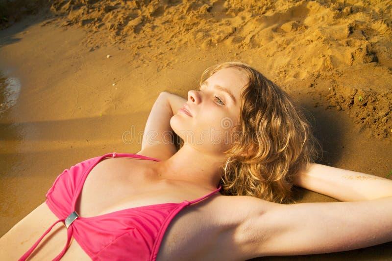 Mulher pensativa nova na praia imagem de stock