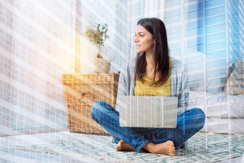 Mulher pensativa nova que senta e que olha a janela fotos de stock