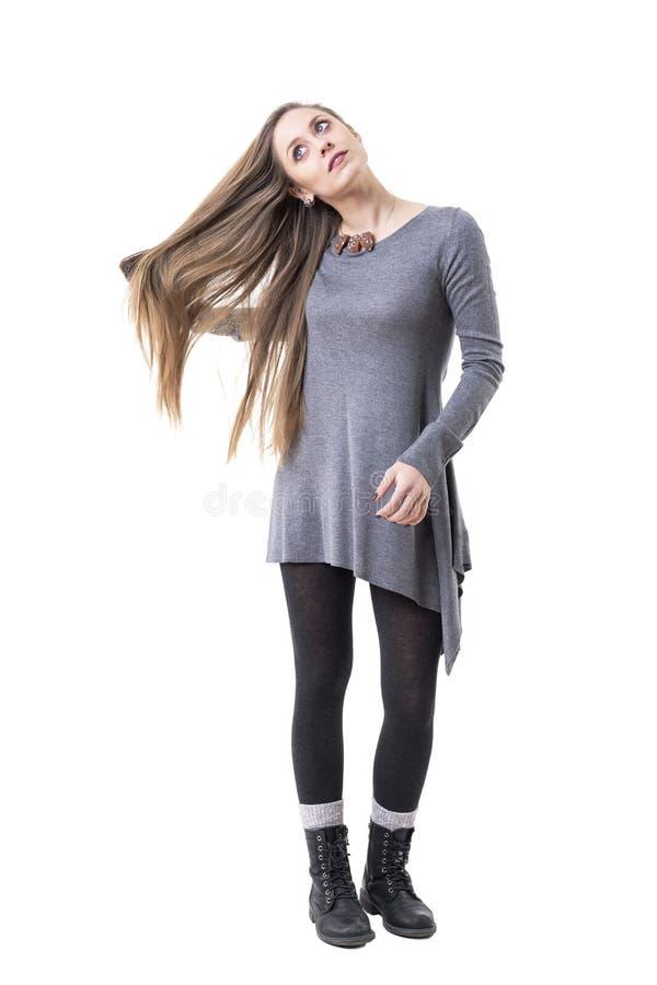 Mulher pensativa nova relaxado que olha acima sonhando acordado ao escovar seu cabelo longo fotos de stock royalty free