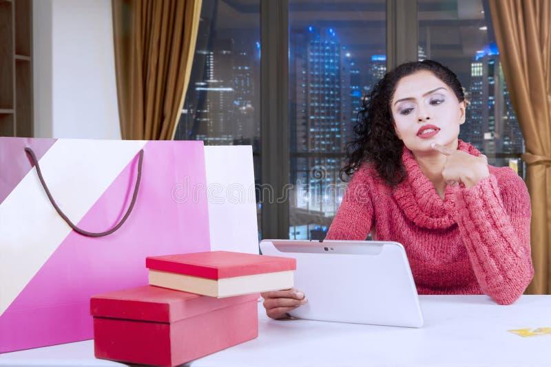 Mulher pensativa que compra em linha no apartamento imagens de stock royalty free