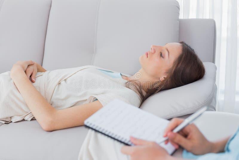 Mulher pensativa que encontra-se no sofá quando escrita do psicólogo imagens de stock