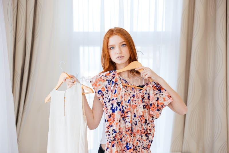 Mulher pensativa que escolhe a roupa pôr sobre fotografia de stock