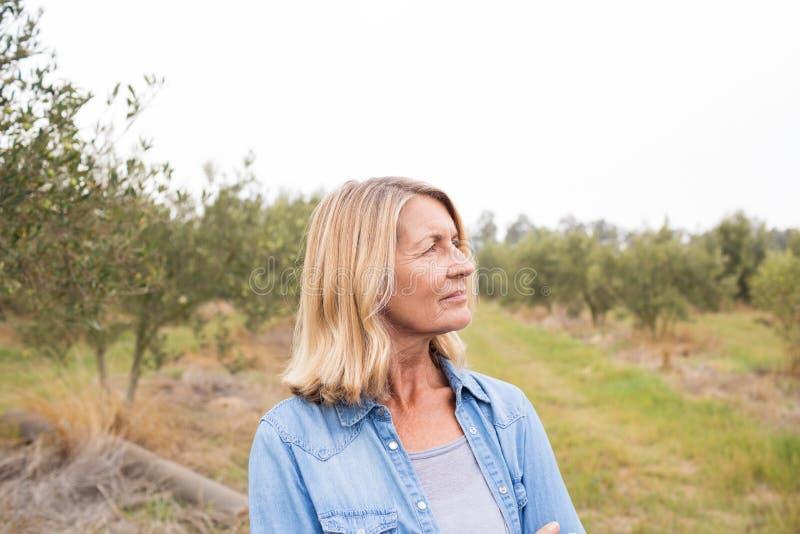 Mulher pensativa que está no campo verde-oliva imagem de stock