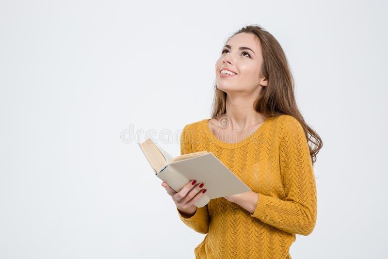Mulher pensativa que guarda o livro e que olha acima imagem de stock royalty free