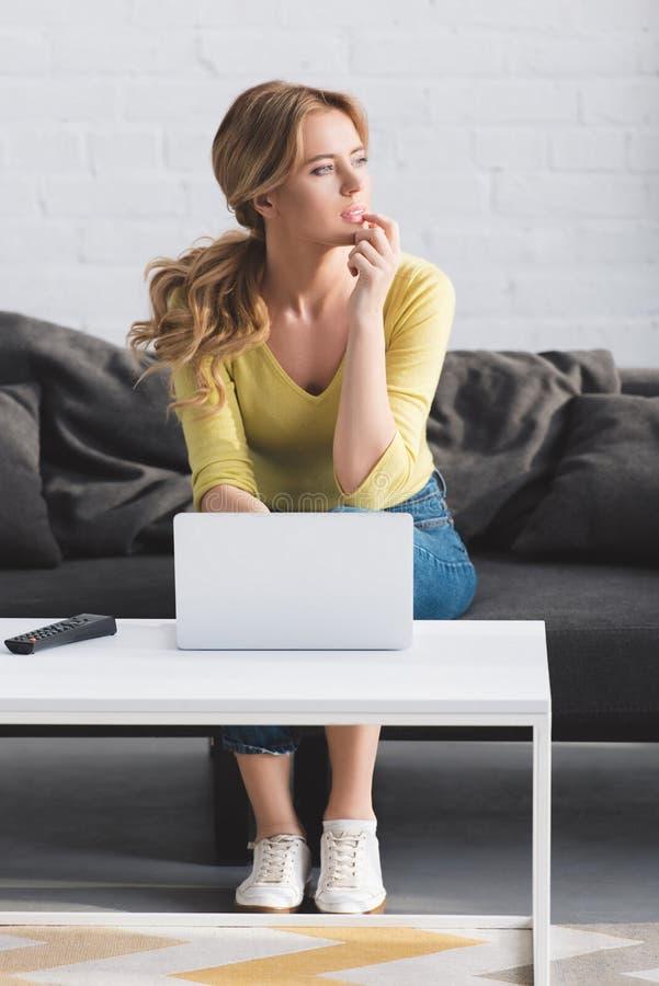 mulher pensativa que olha afastado ao sentar-se no sofá e foto de stock
